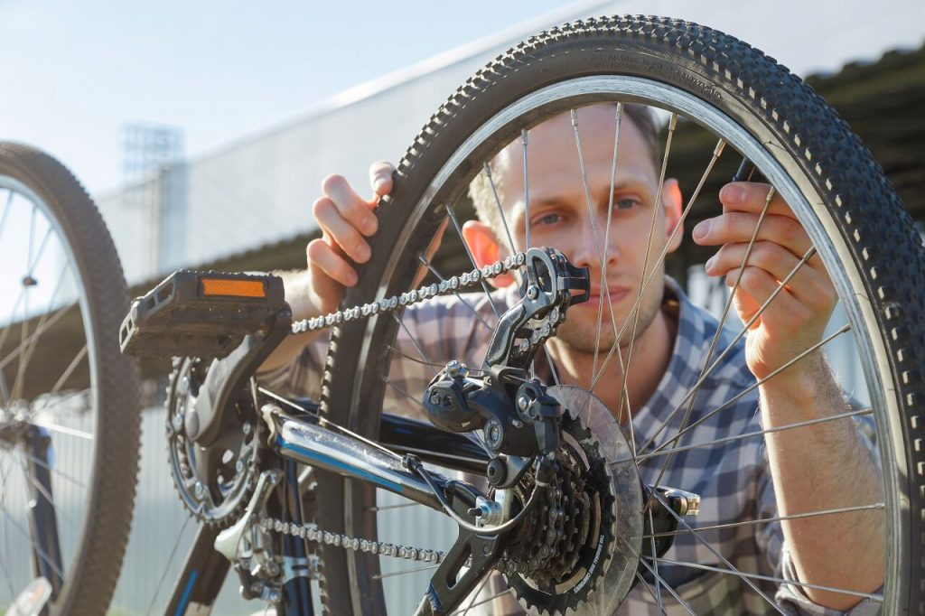 man fixing his bicycle wheel